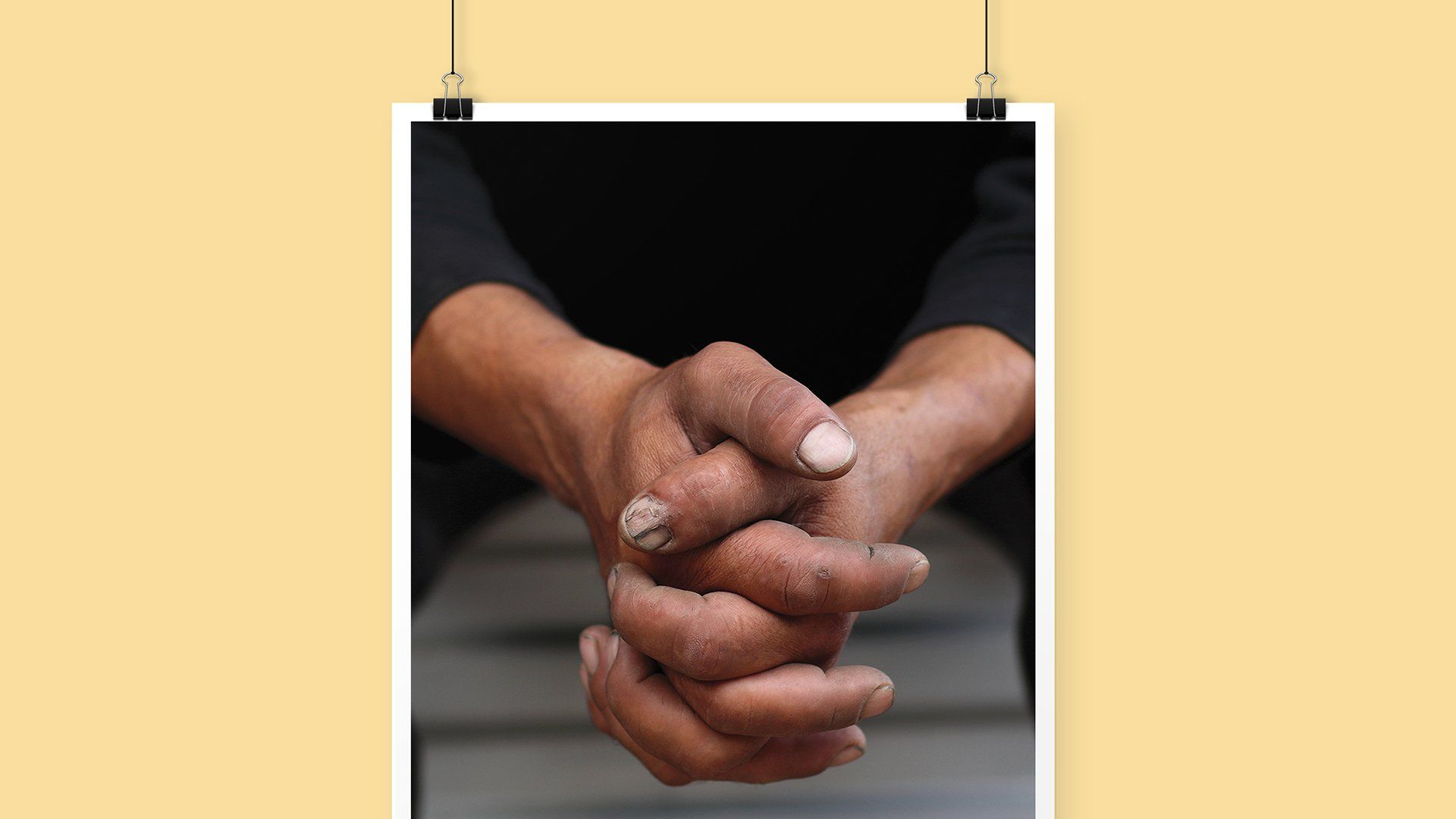 A beautiful print poster showing a profound image of a male with his hands interlocked.